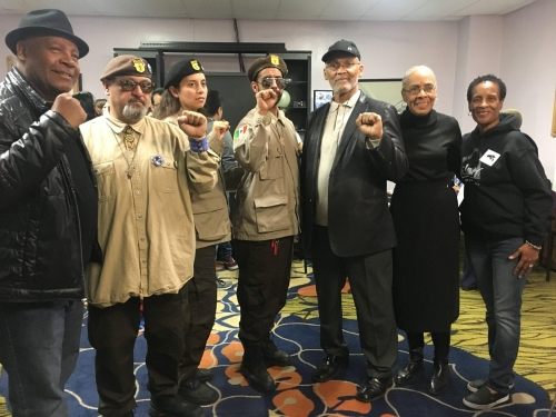 """Bruce A. Dixon and other former Black Panthers along with the Brown Berets raise their fists and chant """"All Power to the People"""" at the 50th Anniversary of the Illinois Chapter of the BPP at a West Side Health Fair in November. https://www.gp.org/bruce_a_dixon"""